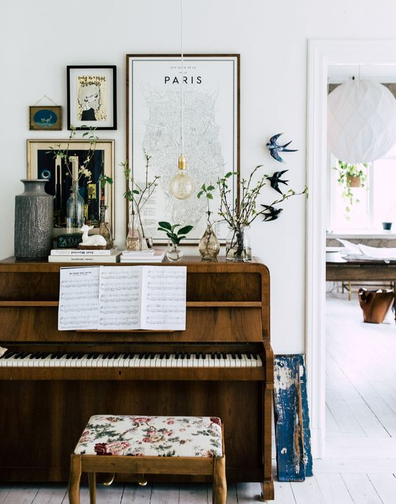 a cool piano, an upholstered stool and a gallery wall with signs and artworks, greenery and flowers in vases on display