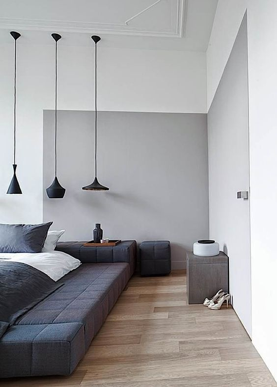 a grey element and a black upholstered podium bed for an edgy color block bedroom look