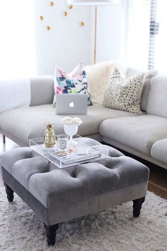 a grey upholstered ottoman doubles as a cool coffee table