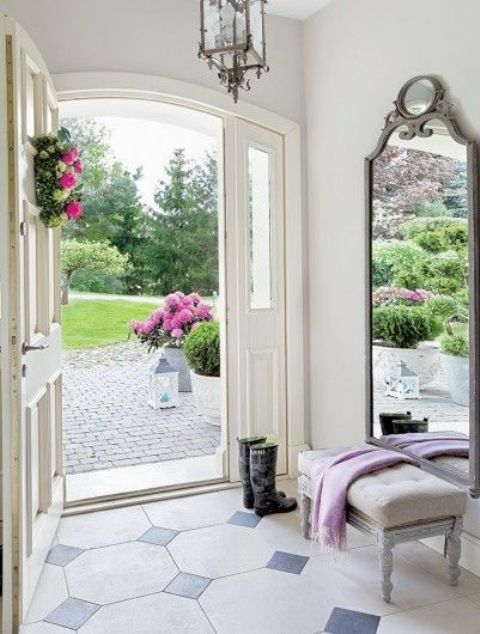 a large mirror in a vintage grey frame with chic detailing for a country chic entryway