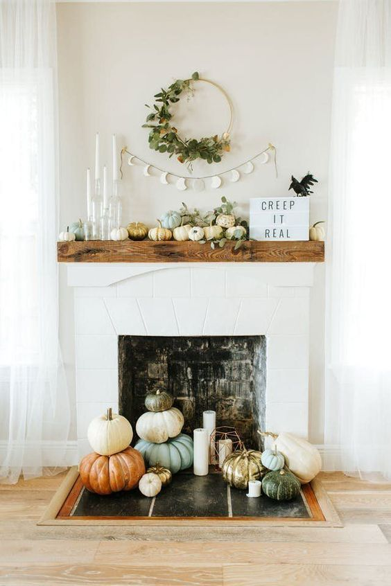 a modern and natural mantel with pumpkin, eucalyptus, candles, signs and a fake bird