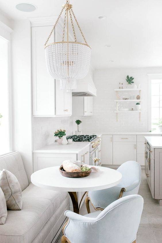 a neutral kitchen with a separate nook for having meals, with comfy refine dchairs and a large banquette seating