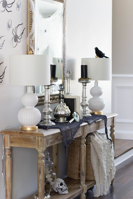 a rustic console with a bird, a skull, some spiderweb and black candles in tall candleholders