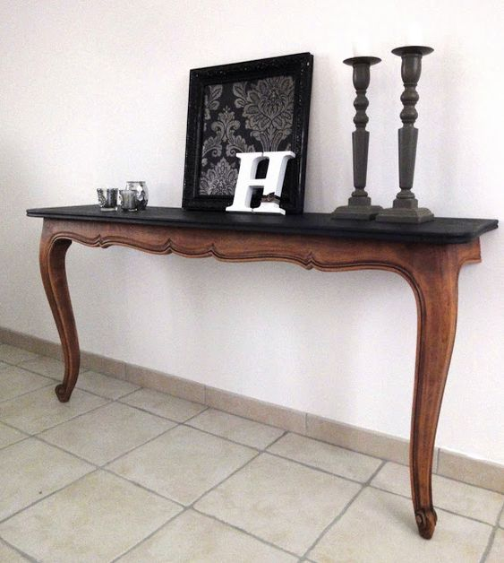 a super elegant console table cut in halves with a black wooden tabletop for a living room