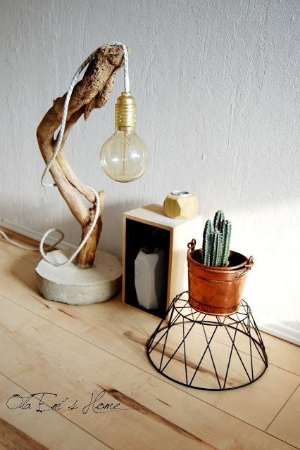 an eye catchy table lamp of concrete, a curved tree branch and a large bulb is great for many decor styles