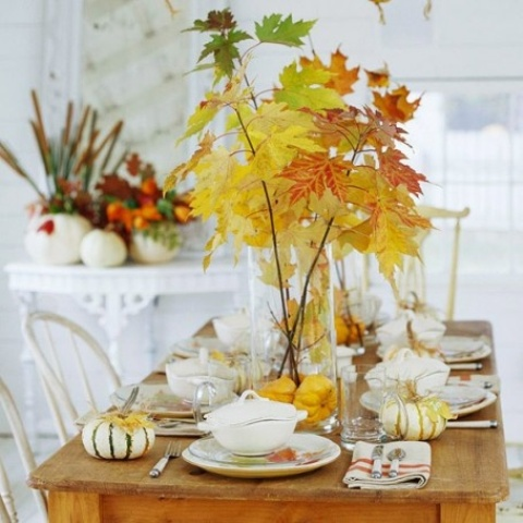 fall leaves in a large sheer vase with pumpkins on the bottom is a modern fall centerpiece
