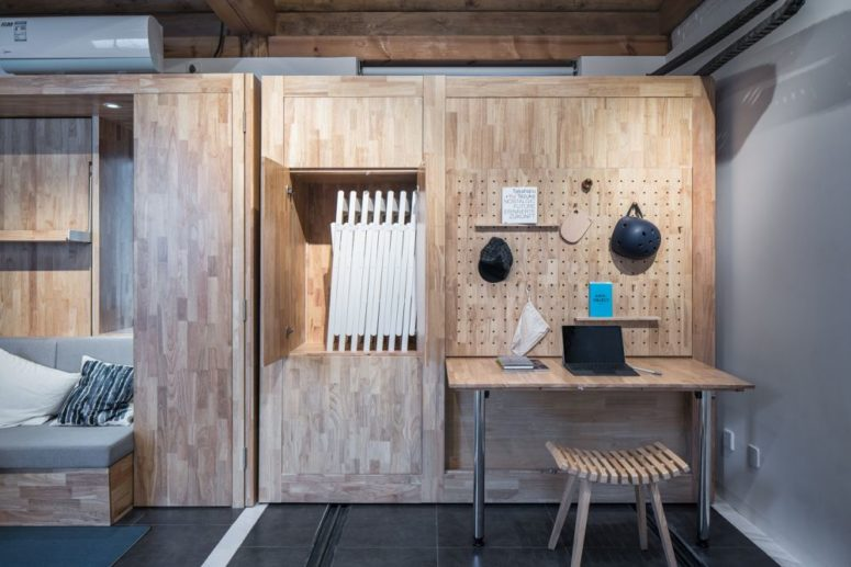 A small desk is built into one of the furniture modules, together with a pegboard and a storage compartment for the dining chairs
