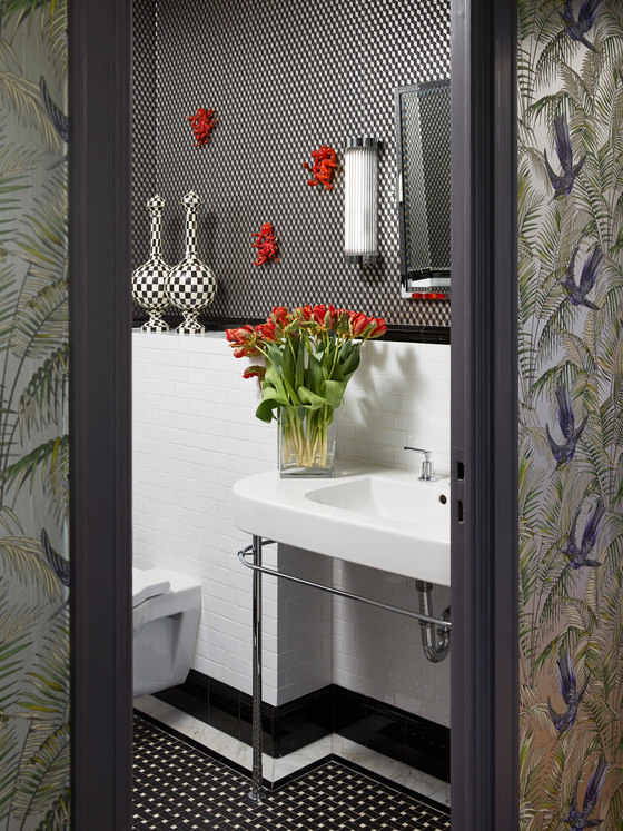 The bathroom is done in black and white with catchy patterns and red touches