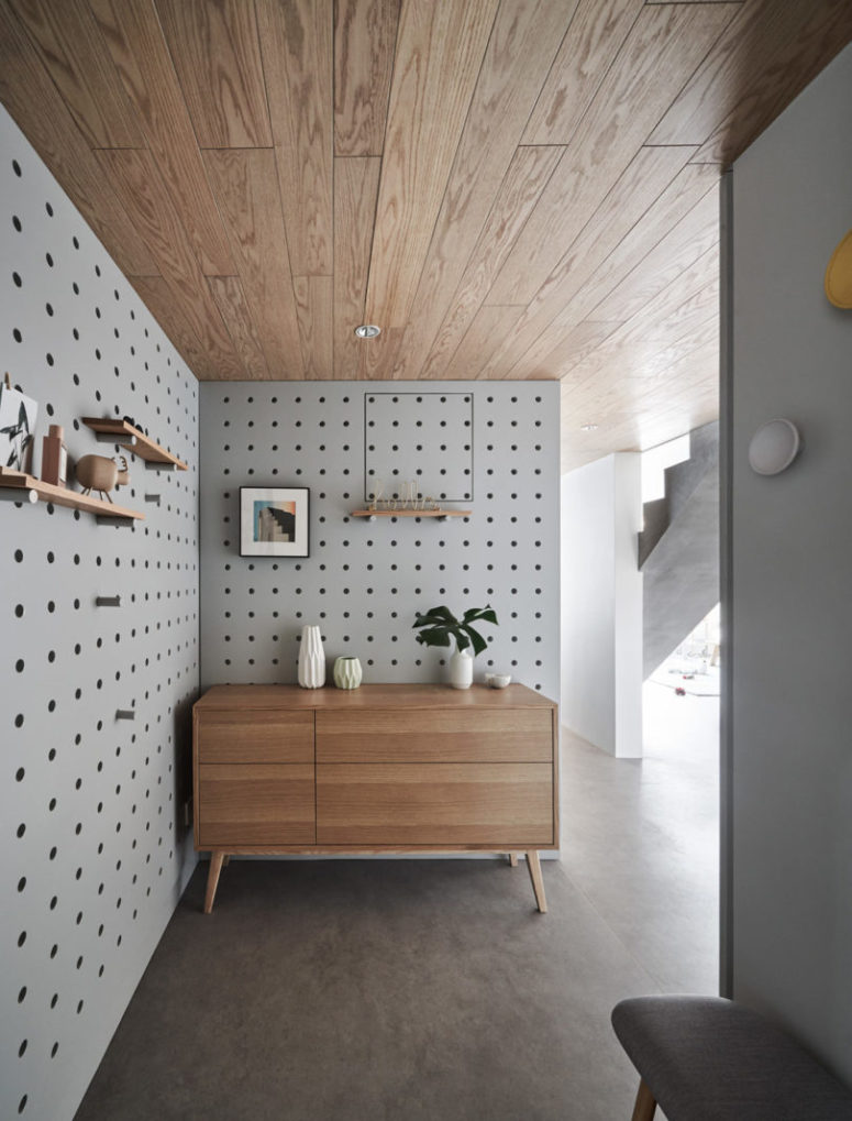 The entryway is covered with pegboard and modern furniture, with shelves and potted plants