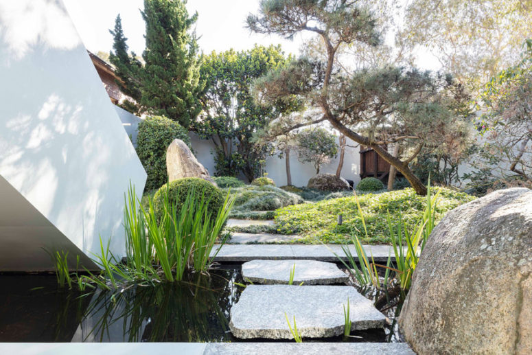 The garden is perfectly styled, with water features and large rocks