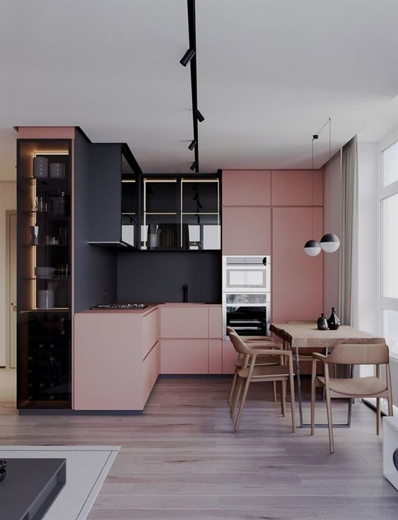 a contemporary color block kitchen in pink and black with a sleek and stylish look and a wooden dining set