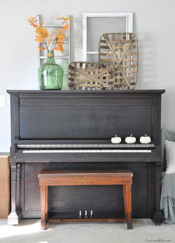 a fall display with frames, fake pumpkins, fallfoliage and wood strip bowls on the piano