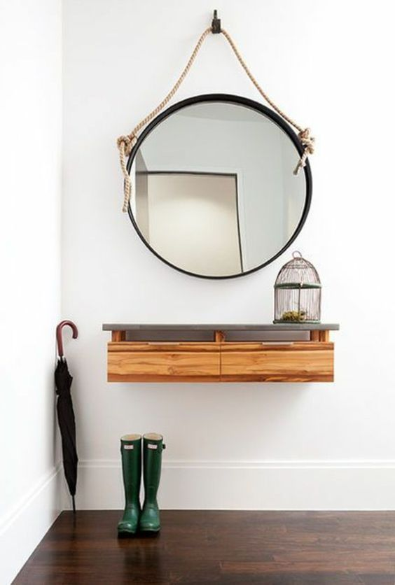 a floating console of wood with a concrete tabletop and a framed mirror with rope for a coastal space