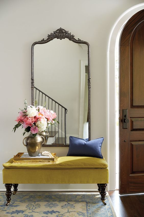 a large vintage mirror in a silver frame and a mustard velvet bench make up a gorgeous entry