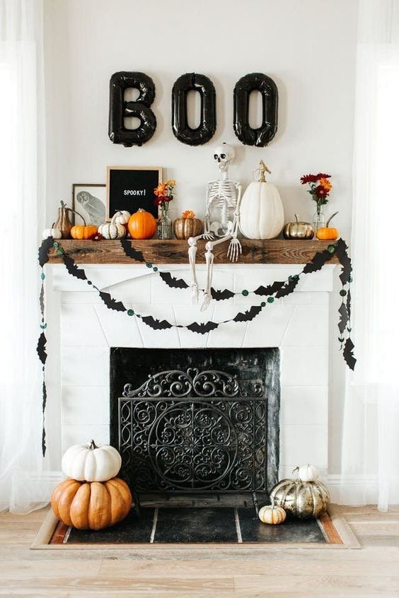 a modern Halloween mantel with a skeleton, balloon letters, buntings, pumpkins and signs