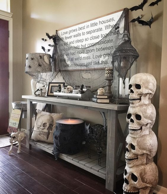 a rustic console with black bats and spiders, black spiderweb and a lit up cauldron plus skulls