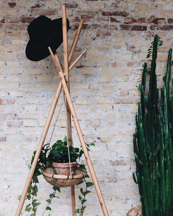 a wooden coat rack made of wood sticks and with a suspended planter in a basket to enliven your space