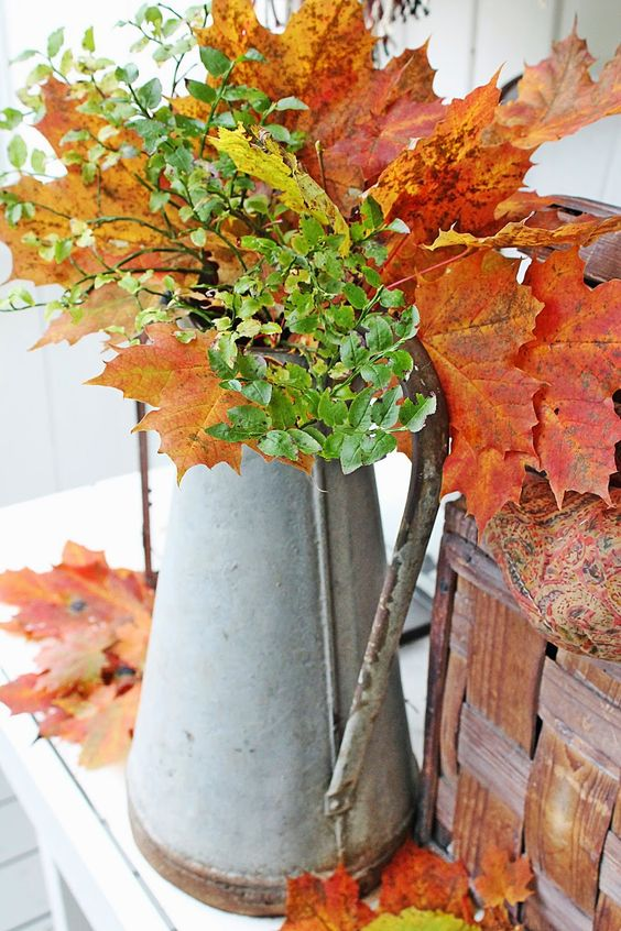 an antique metal jug with fall leaves and greenery for home decor is a great idea for a rustic space