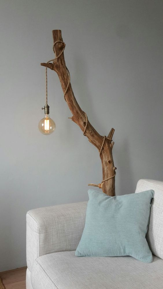 cover a stained tree branch with an industrial pendant light with a cord and a large bulb for making a cool lamp