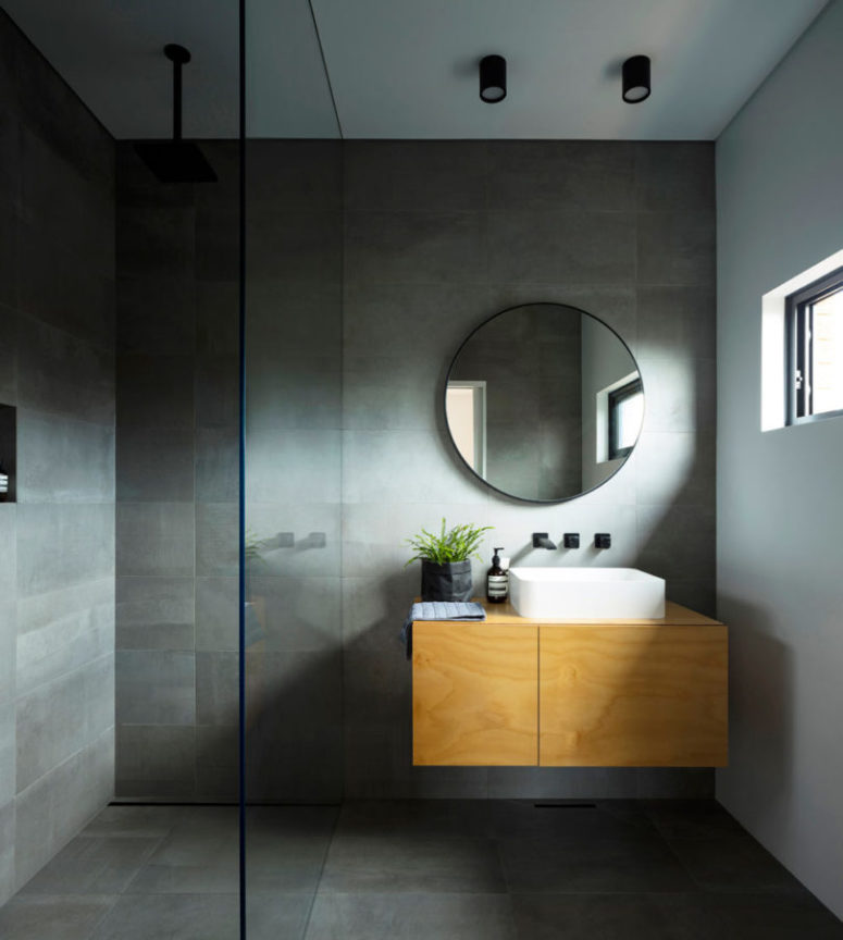 There's also another bathroom with grey stone-like tiles and a shower