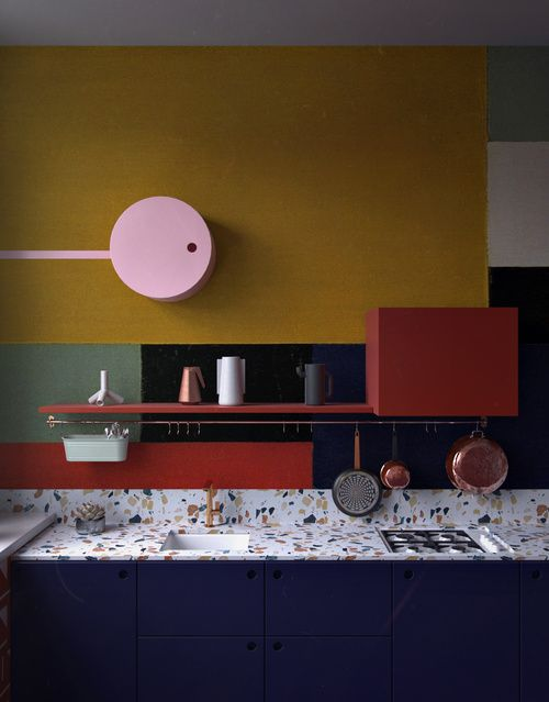 a dark blue kitchen with a terrazzo countertopp, brass fixtures and postal red shelf plus green and yellow color blocking