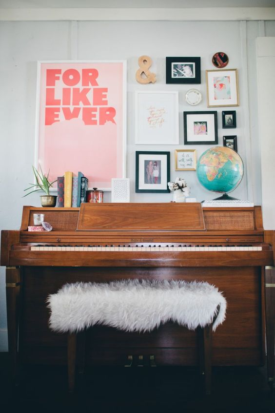 a gallery wall with signs, photos, artworks in various colors over the piano for a cool and chic look