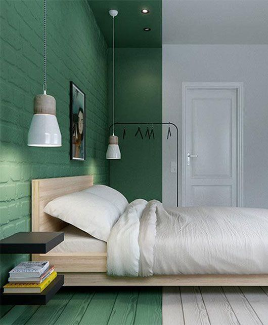a minimalist bedroom with a sleeping zone accented with bright green color on the walls, ceiling and floor