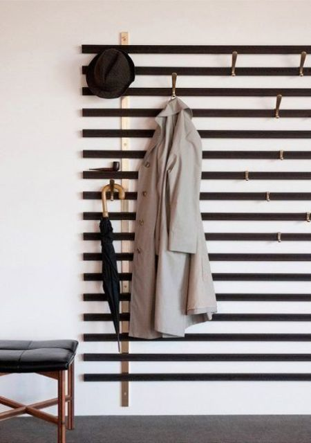 a simple wall-mounted hanger of wooden slabs and hooks attached where necessary - you won't need more for a small space