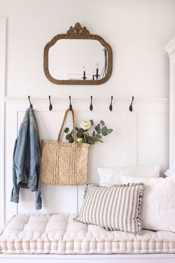 a small mirror in a vintage metallic frame is ideal for a cozy cottage entryway