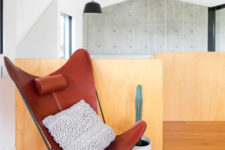 14 The upper floor meets the owners with a bold red leather chair