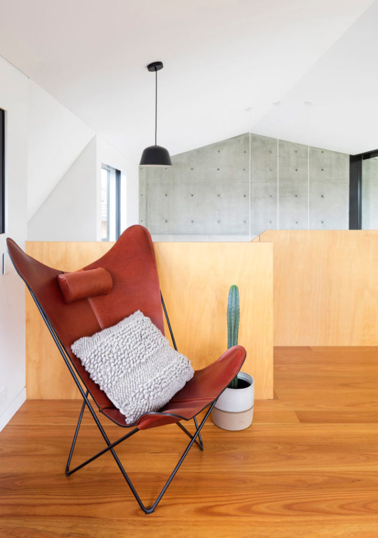 The upper floor meets the owners with a bold red leather chair
