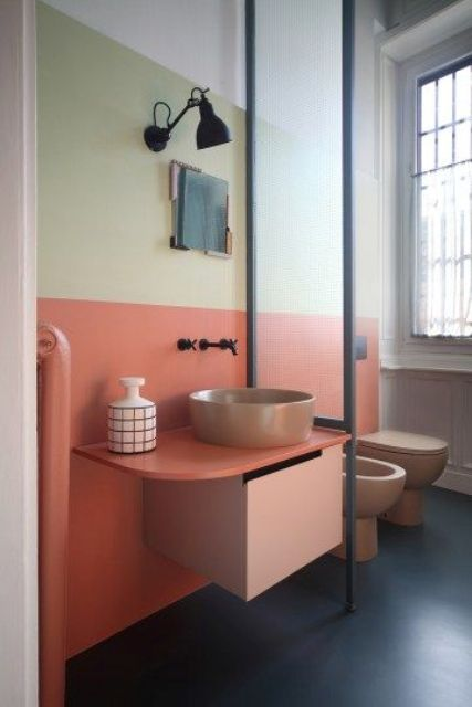 a light yellow and coral plus matching pinkish fixtures for the powder room to give it a mid-century modenr feel