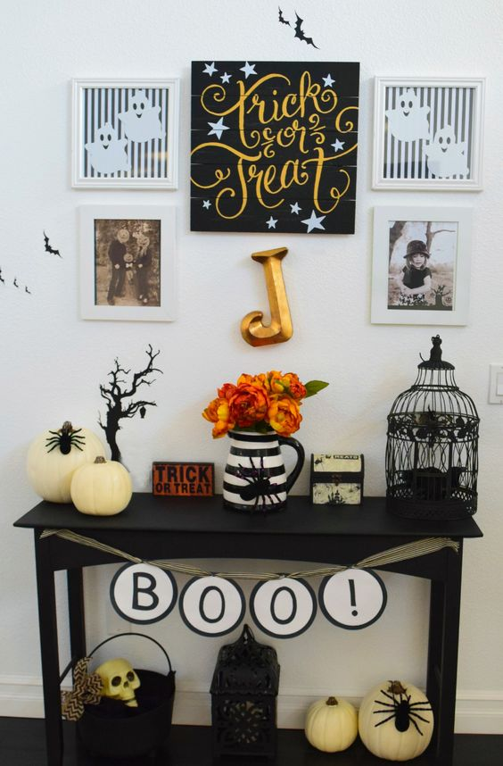 a small console with faux pumpkins, a cage, letters, a psider and some artworks