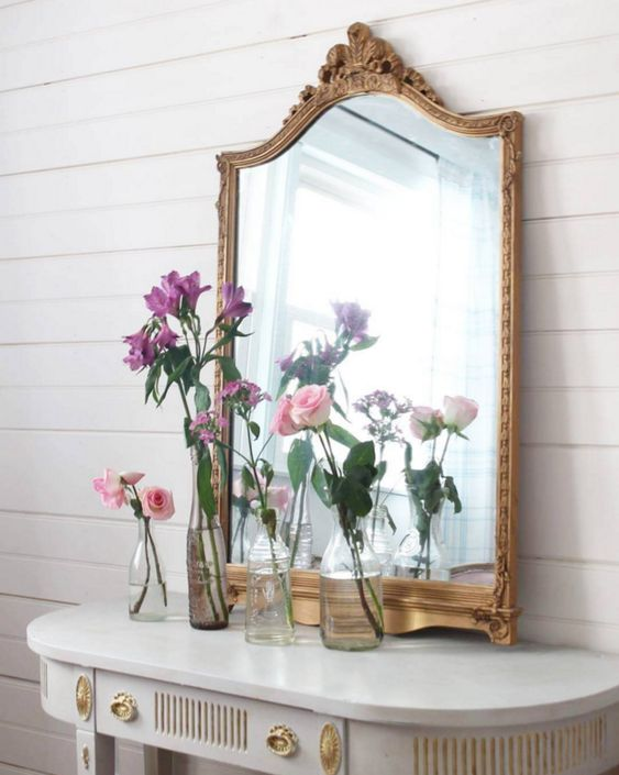 an antique white and gold console and a refined mirror in a vintage gold frame for a chic feel
