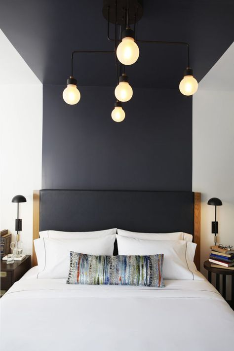 for making your space ultra-modern, just go for color blocking, like here a black headboard flowing into the wall and ceiling over the bed