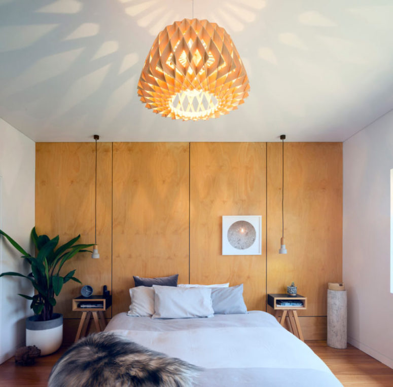 The master bedroom is done with pendant lamps and plywood panels plus nightstands