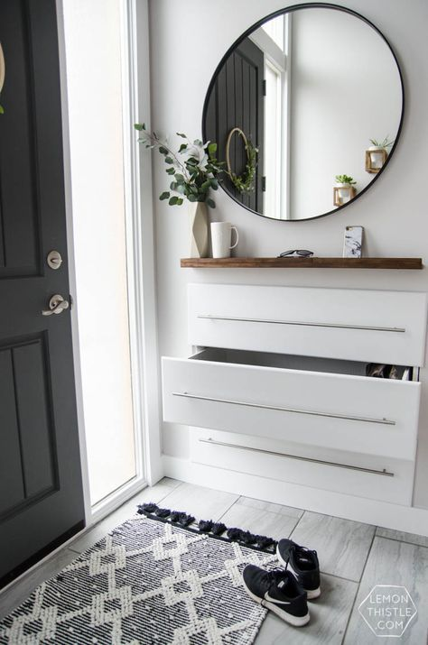 a modern entryway floating console with neutral pulls and a wooden shelf over it