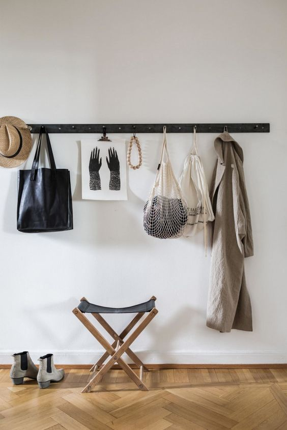 a simple wooden strip with metal hooks is a perfect fit for a minimalist space and an easy DIY project
