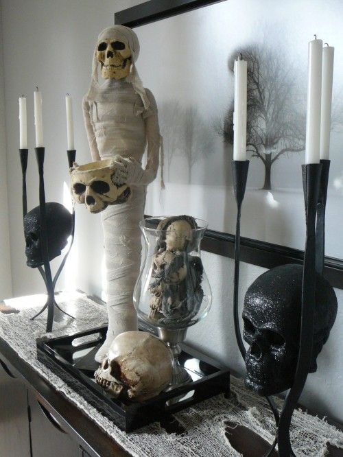 a spooky console display with skulls and a mummy plus candles and a haunted scenery on the artwork