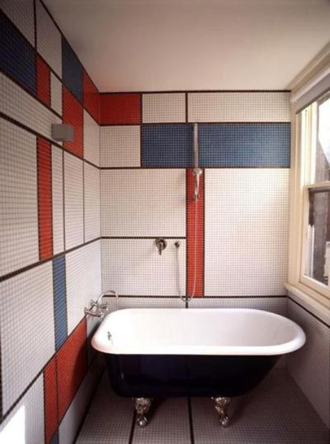 bathroom walls clad with tiles with a color block effect, in white, blue and red make the space stand out