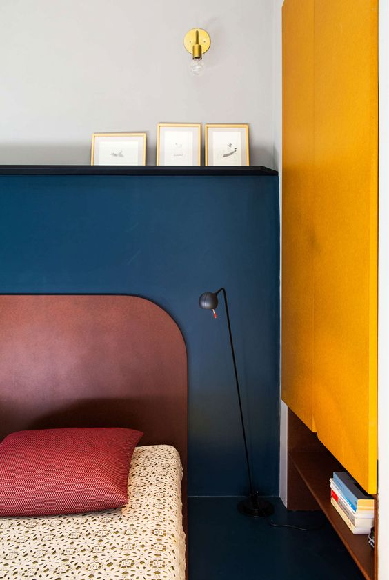 stylish color blocking with a navy headboard wall and a bright yellow wall on the right