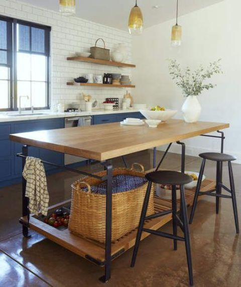 a chic kitchen with an industrial kitchen island of wood and metal plus storage space and tall stools