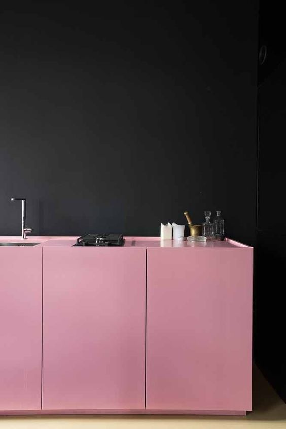 a contemporary kitchen with only lower cabinets in bold pink and a black wall for a juxtaposition