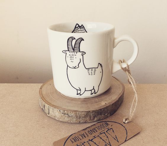 a fun and quirky goat mug on a wood slice coaster