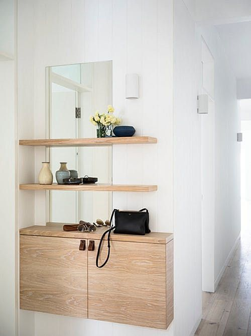 a plywood console and a duo of matching shelves over the console for a comfy contemporary space