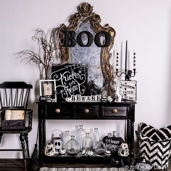 a spooky Halloween console in black and white with painted pumpkins and signs plus a vintage mirror