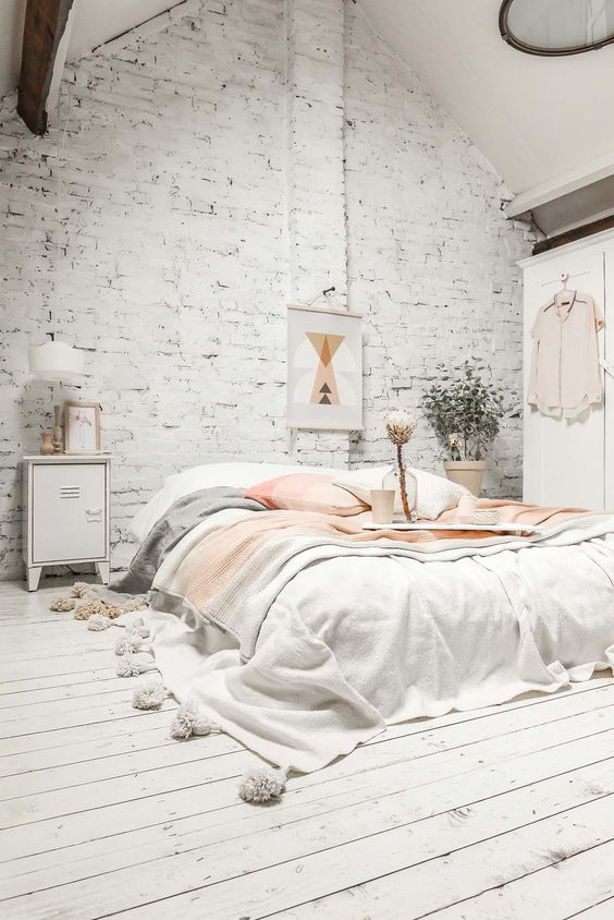 a whitewashed brick wall and a whitewashed wood floor make the space interesting playing with textures