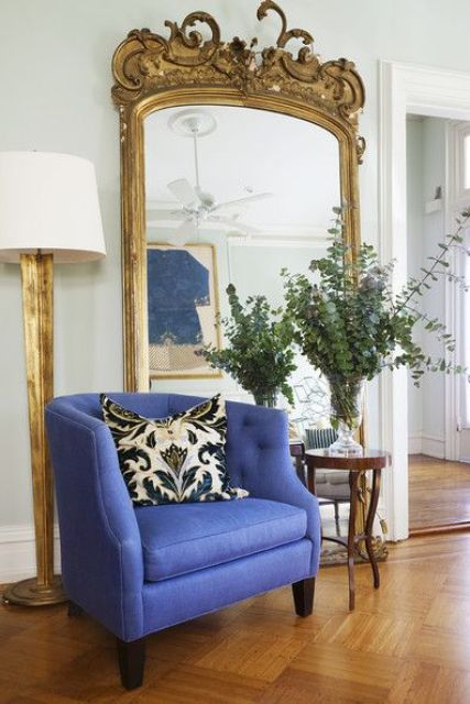an oversized mirror in a gorgeous vintage frame with vignettes and various detailing on the top