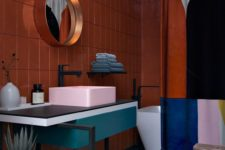 17 a bold color blocked bathroom with a rust wall, a pink sink, a teal vanity and a color blocked shower curtain to match