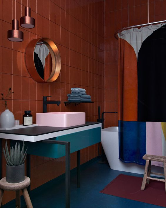 a bold color blocked bathroom with a rust wall, a pink sink, a teal vanity and a color blocked shower curtain to match